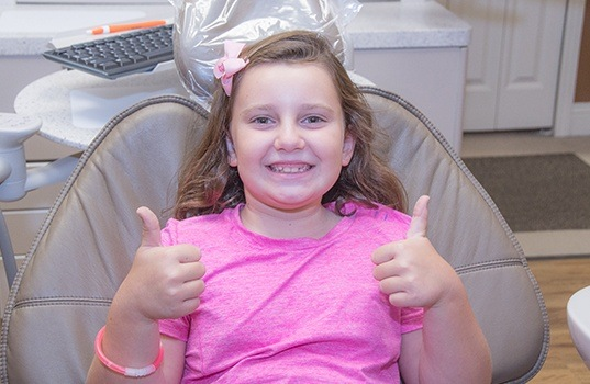 Young girl in dental chair giving two thumbs up