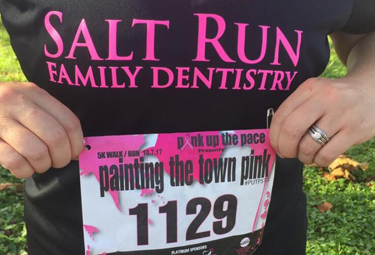 Salt Run Family Dentistry team member holding up race number at fun run