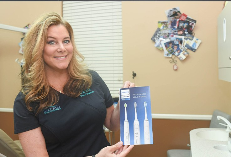 Dental team member holding an electric toothbrush