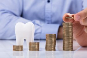 Piles of coins and tooth showing cost of dental implants